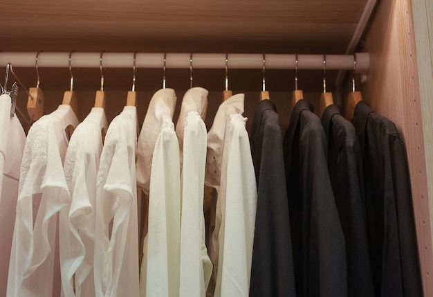 Camicie bianche e nere su trempele nell'armadio