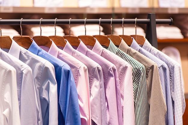 Camicie da uomo su appendiabiti, fila di camicie colorate nel centro commerciale