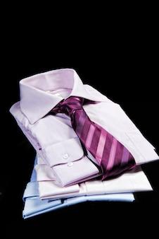 Camicie piegate con cravatta sullo sfondo nero.