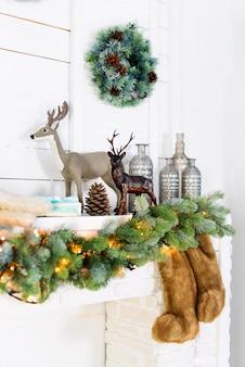 Caminetto con decorazioni natalizie. accogliente scena invernale. dettagli interni bianchi con luci.