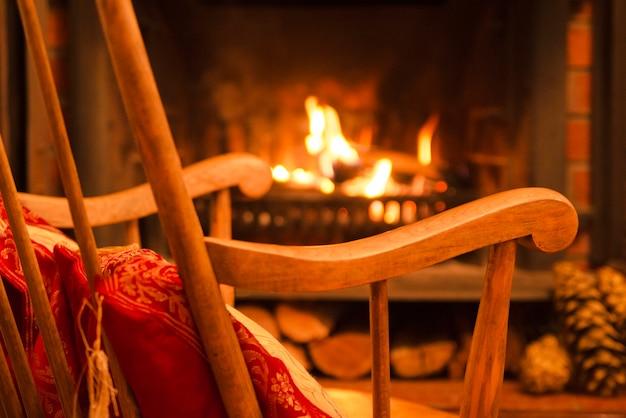 Caminetto e sedia in legno a dondolo. riscaldando nella stagione fredda. serata a casa.