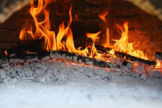 Camino con il fuoco di legna della stufa dell'argilla bruciante del ceppo nella casa nell'inverno - concetto della stanza del camino