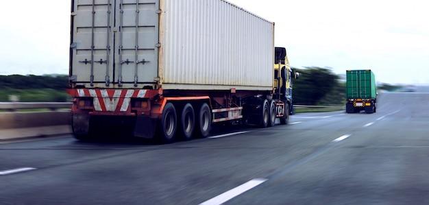 Camion bianco e verde del contenitore sulla strada principale, concetto del trasporto., importazione, esportazione trasporto logistico industriale trasporto terrestre sulla superstrada dell'asfalto
