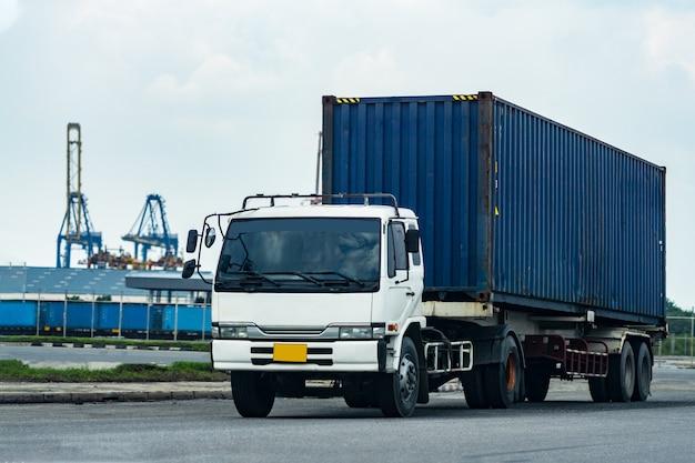 Camion blu del contenitore di carico nella logistica del porto della nave. industria dei trasporti nel concetto di affari del porto.
