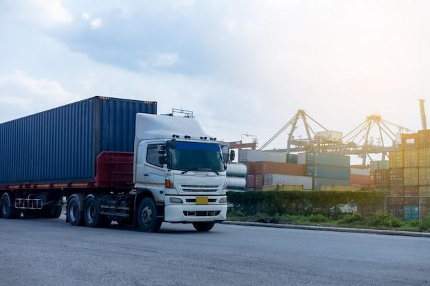Camion blu del contenitore nella logistica del porto marittimo