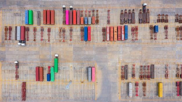 Camion dei semi di vista aerea con parcheggio del rimorchio del carico con altri camion sul parcheggio del porto industriale.