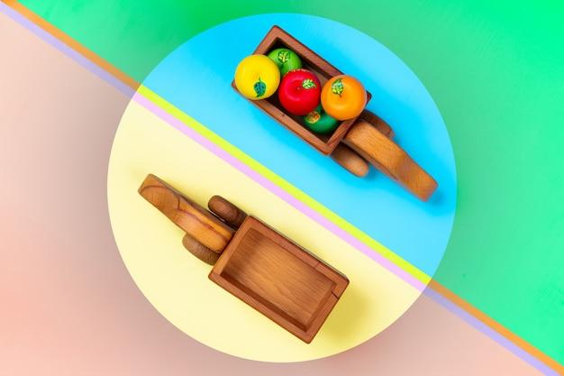Camion di giocattoli di legno con le mele su uno sfondo geometrico vibrante multicolore isolato.