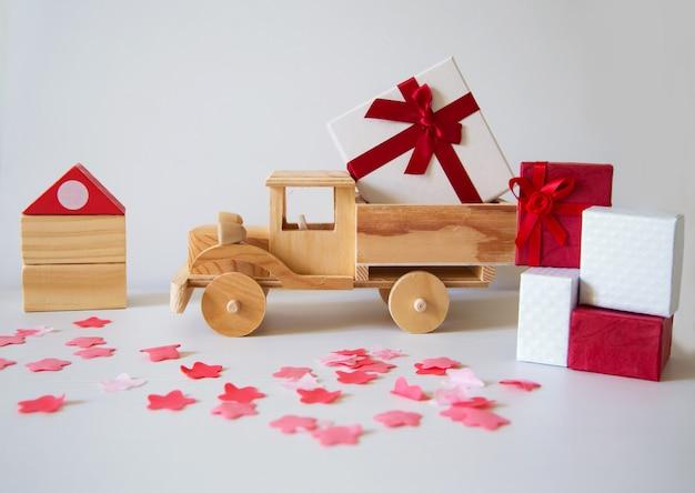 Camion di legno che arriva a una casa e pieno di regali e pacchetti