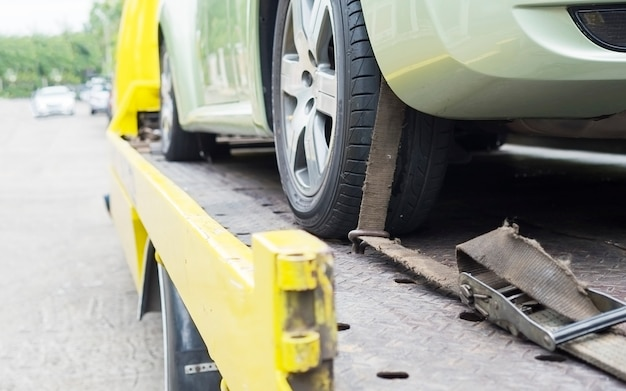 Camion di soccorso stradale durante il lavoro utilizzando la cintura bloccata per il trasporto di altre auto verdi