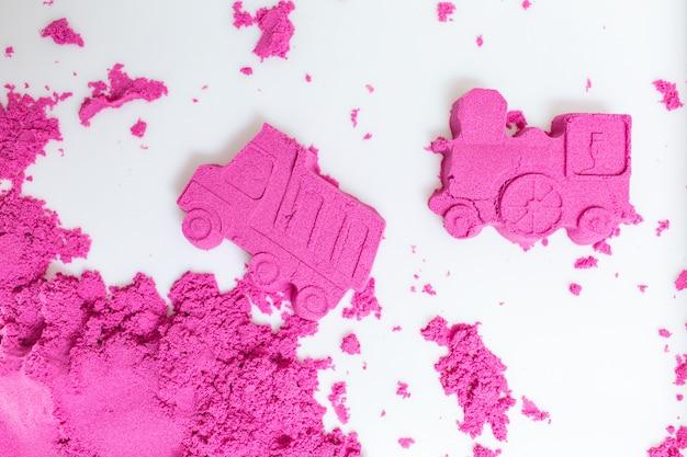 Camion e treno realizzati con una sabbia cinetica rosa su uno sfondo bianco.
