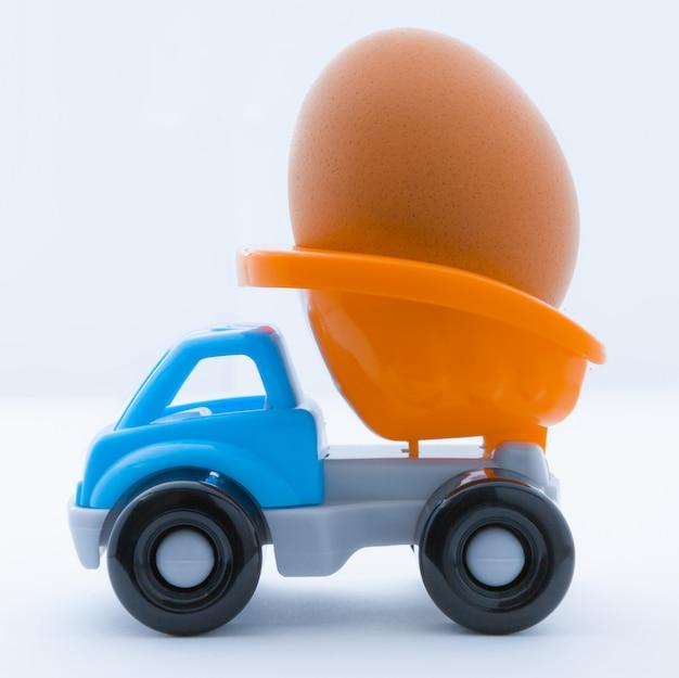 Camion giocattolo colorato con un uovo di gallina nella parte posteriore su uno sfondo bianco