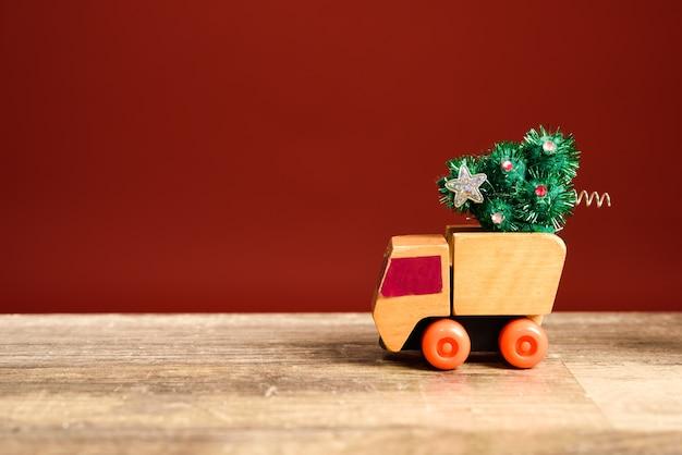 Camion giocattolo piccolo che porta un albero di natale