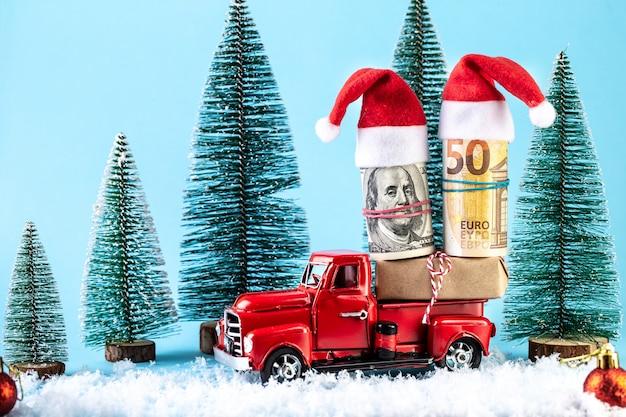 Camion giocattolo retrò che trasporta un regalo di natale soldi