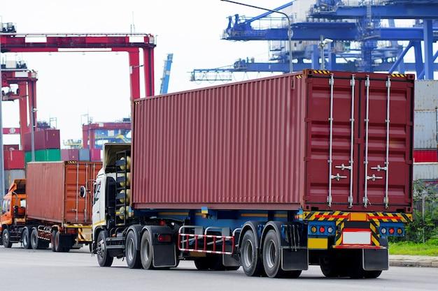 Camion rosso del contenitore di carico nella logistica del porto marittimo