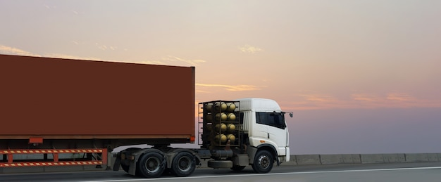 Camion sulla strada della strada principale con il contenitore rosso, industriale logistico con il cielo di alba