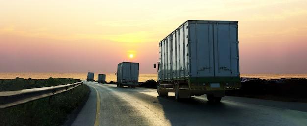 Camion sulla strada della strada principale con il contenitore, trasporto industriale logistico con il cielo di alba