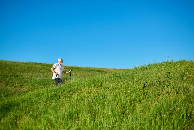 Camminando con i bastoncini di monitoraggio all'aria aperta tra le colline erbose.
