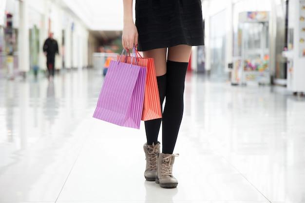 Camminare con le borse della spesa, vicino delle gambe femminili