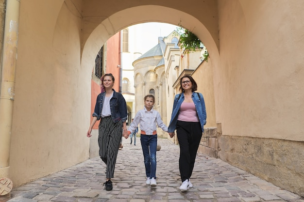 Camminare madre e due figlie che tengono le mani
