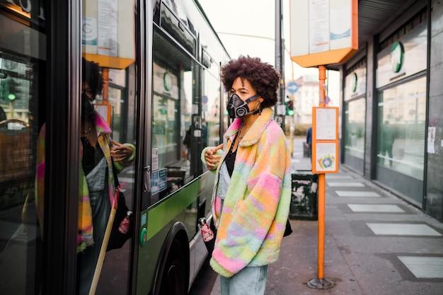 Camminata della giovane donna all'aperto a milano che indossa maschera medica che protegge da inquinamento e virus
