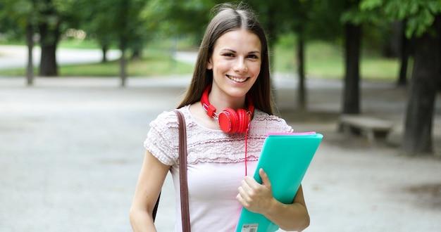 Camminata della tenuta della studentessa all'aperto nel parco e nel sorridere