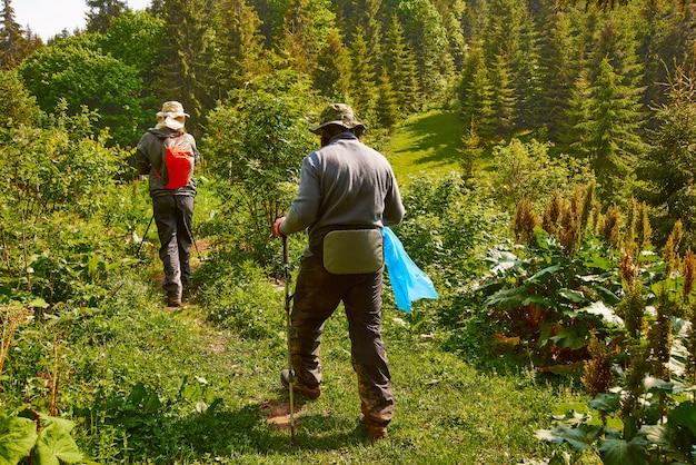 Camminata di due uomini attraverso la foresta alta nelle montagne con un sacchetto di immondizia. proteggere la natura