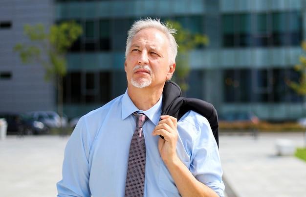 Camminata matura dell'uomo d'affari all'aperto in una regolazione moderna della città