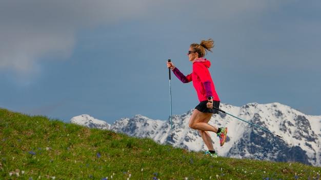Camminata nordica e trail running una ragazza con bastoncini su orate di montagna di primavera con sfondo innevato