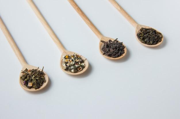 Camomilla asciutta di vista dell'angolo alto in cucchiaio con le erbe del tè.