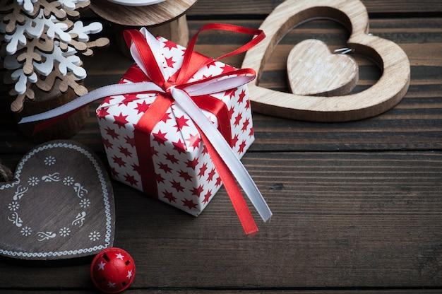 Campana di natale, candela, abeti, giocattoli, regali rossi