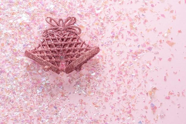 Campana jingle vintage su glitter rosa. natale minimo. felice anno nuovo. vista piana, vista dall'alto, copyspace