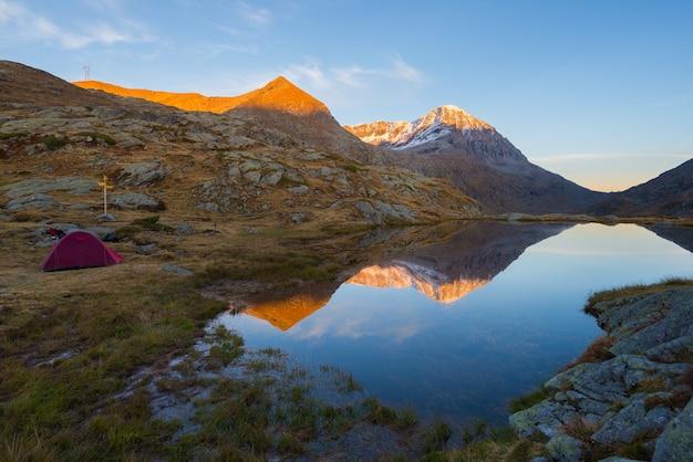 Campeggio con tenda vicino al lago d'alta quota sulle alpi. riflessione di catena montuosa innevata e cielo variopinto scenico al tramonto. avventura ed esplorazione.