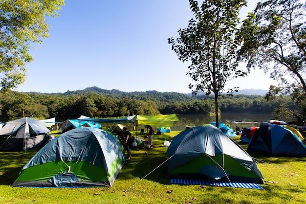 Campeggio di ecoturismo, escursionismo e concetto di tenda campeggio e tenda vicino al lago e sotto la foresta nel tramonto