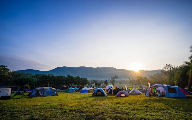 Campeggio e tenda nel parco naturale con alba dietro la montagna