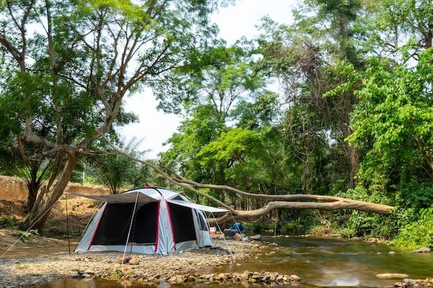 Campeggio e tenda vicino al fiume nel parco naturale