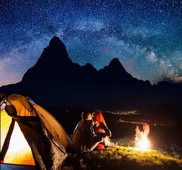 Campeggio notturno turisti vicino al fuoco e tenda sotto le stelle