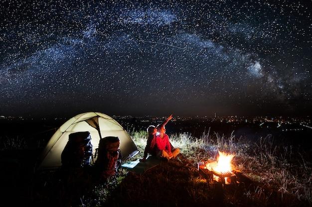Campeggio notturno vicino alla città vicino al fuoco e alla tenda