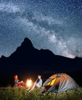Campeggio notturno zaino in spalla felice coppia seduta da falò e tenda sotto incredibilmente bello cielo stellato. silhouette di alte montagne e villaggio nella valle sullo sfondo. lunga esposizione