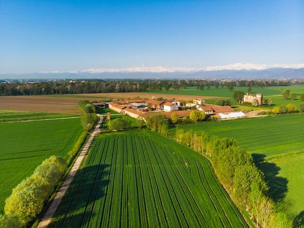Campi coltivati aerei dall'alto, fattoria rurale nella campagna verde italiana con alpi innevate