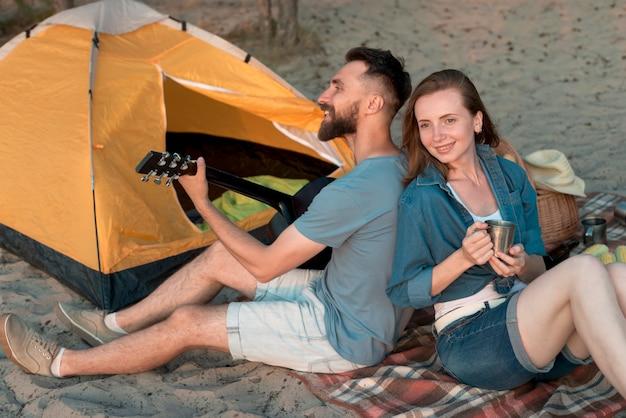 Camping coppia schiena contro schiena, guardando lontano