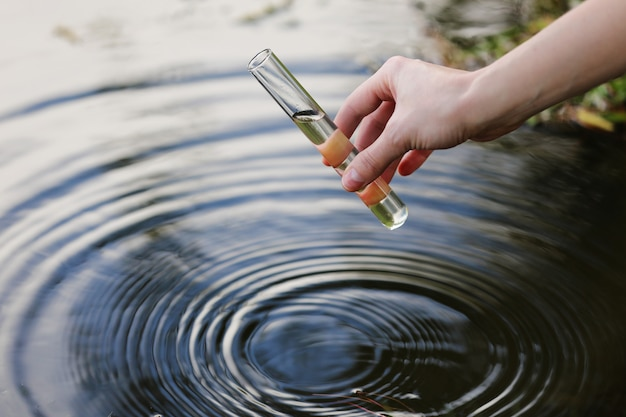 Campione d'acqua. la mano raccoglie l'acqua da esplorare. concetto: analisi della purezza dell'acqua, ambiente, ecologia. test dell'acqua per infezioni, permesso di nuotare. messa a fuoco selettiva, posto per il testo.