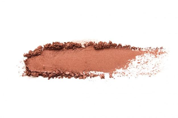 Campione di ombretto isolato. ombretto metallizzato marrone schiacciato. il concetto di moda e industria della bellezza.