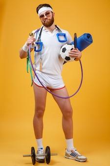 Campione soddisfatto felice dell'uomo che tiene tazza e attrezzature sportive dorate