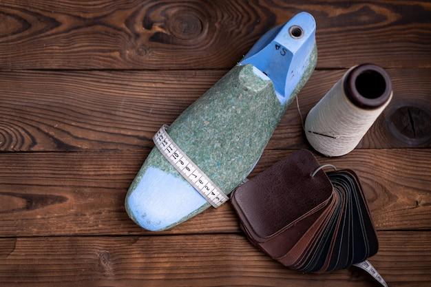 Campioni di cuoio per scarpe e scarpe di plastica durano sul tavolo di legno scuro