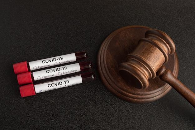 Campioni di sangue infetti in provette covid 19 e martelletto del giudice. punizione per la diffusione dell'infezione
