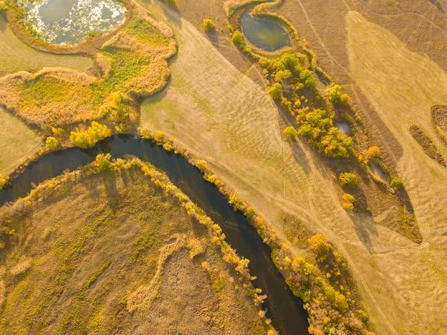 Campo aereo del paesaggio di giallo di autunno con il fiume