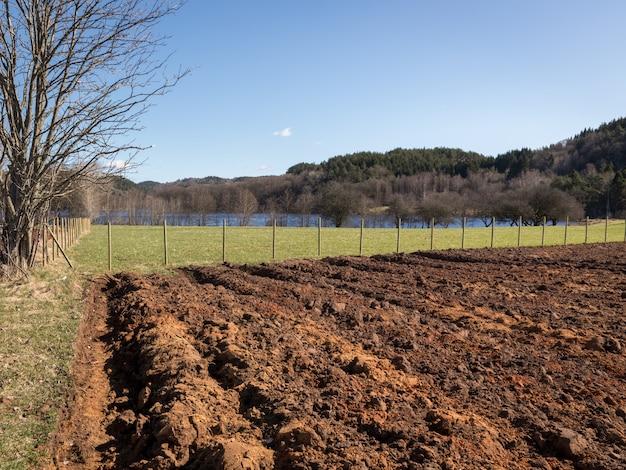 Campo arato nel tempo di primavera, erba verde sui lati, cielo blu.