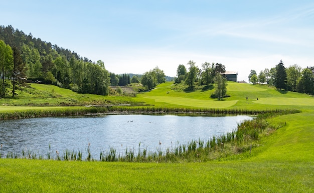 Campo da golf con stagno, cielo blu e natura verde