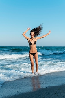 Campo lungo di bella ragazza in spiaggia