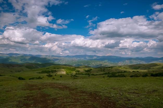 Campo ricoperto di erba circondato da colline coperte di boschi sotto un cielo nuvoloso e luce solare